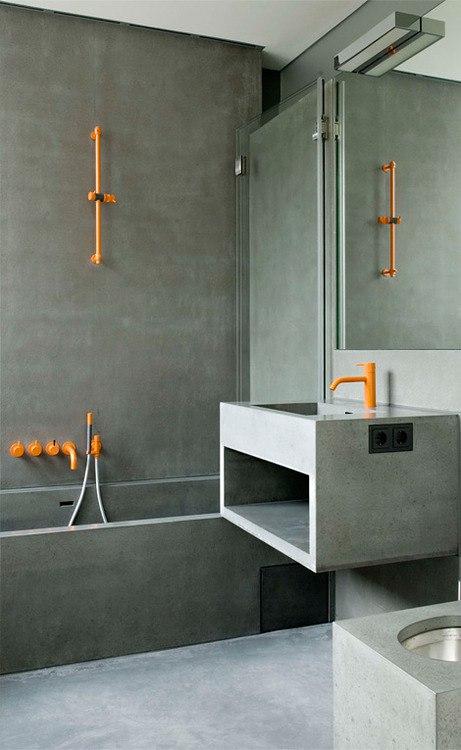 Интересный, современный дизайн: серая отделка ванной комнаты под бетон и яркая сантехника